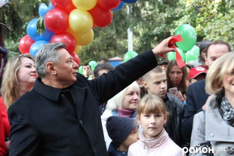 Микола Романюк роздає присутніх фрагменти червоної стрічки