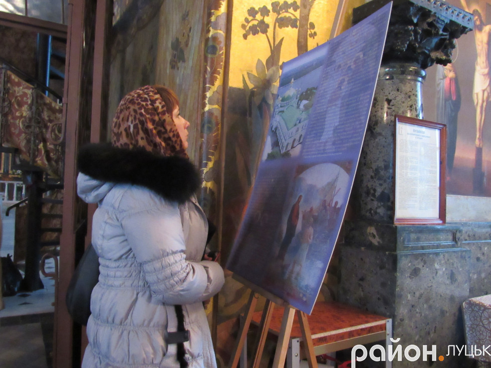 Журналістка Олена Лівіцька приглдається до зображення на мольберті в храмі