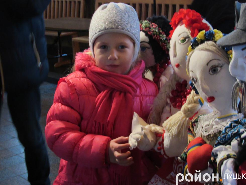 Дівчинка тримається за руку ляльки