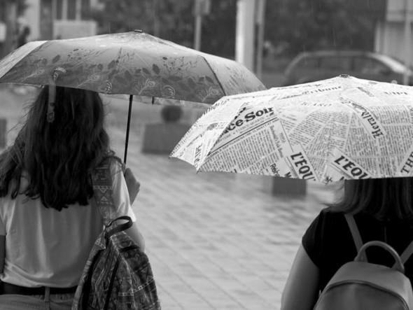 Лучани ховаються під парасолями від літнього дощу