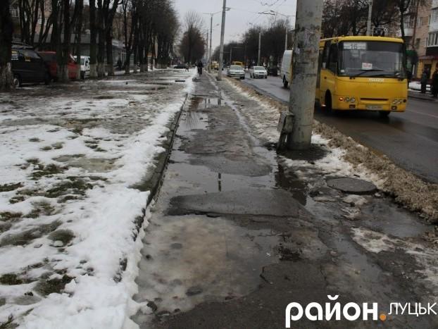 На проспекті Волі у негоду на розбитому тротуарі ями ущент заповнені водою