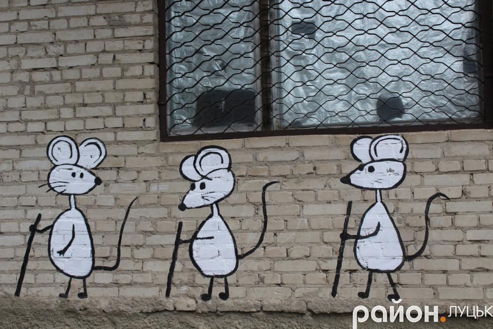 Троє білих мишок мандрує по стіні
