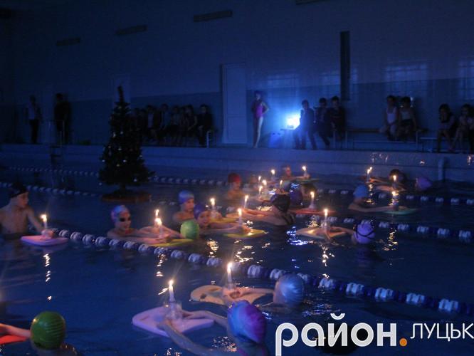 Діти тримають свічки у руках у воді