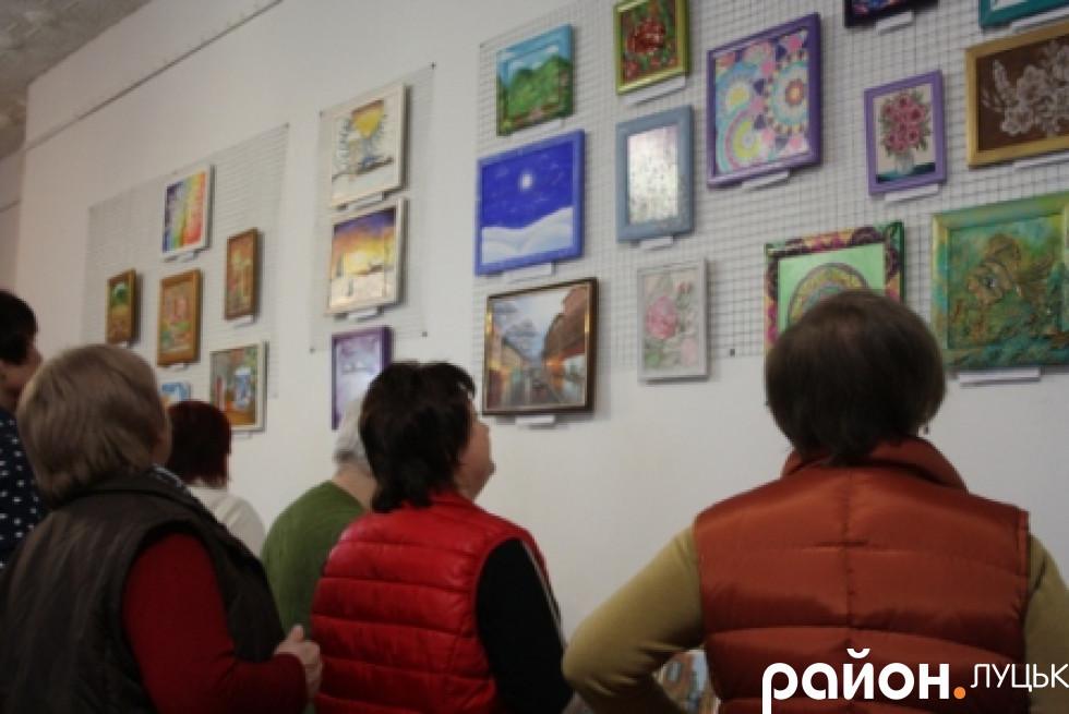 Глядачі розглядають картини
