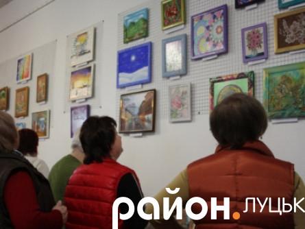 Відвідувачі розглядають картини художниць
