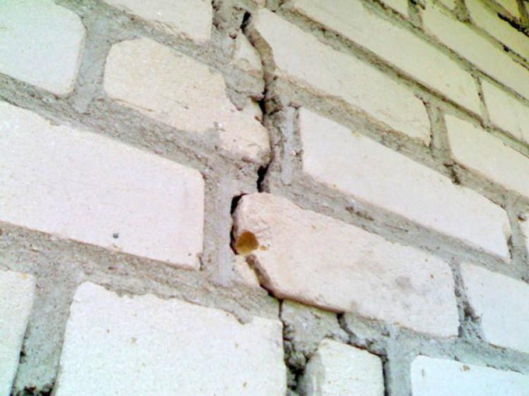 трещины в кирпичной стене снаружи дома