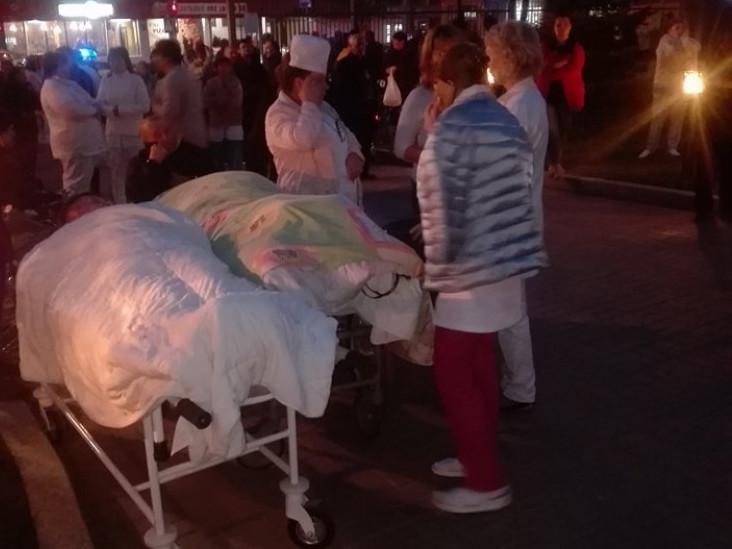 Люди після евакуації заходять назад до лікарні
