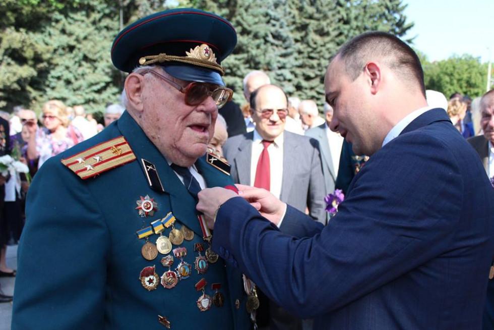 Роман Романюк чіпляє мак ветерану