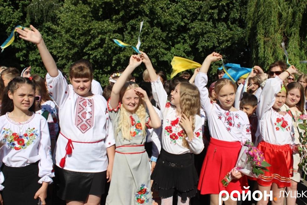 Учні школи махають прапорцями під музичний номер