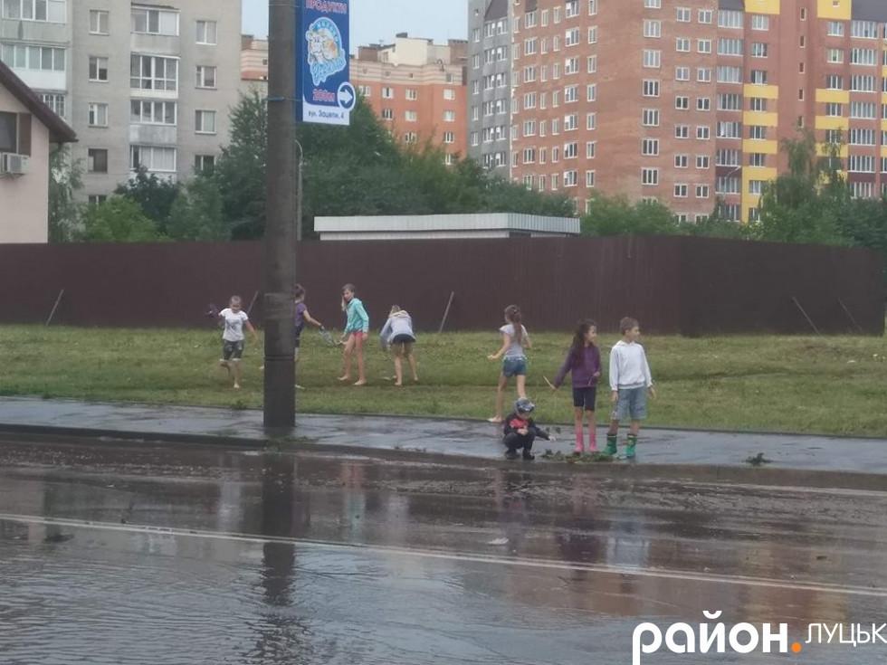 Щасливі діти бігають по калюжах