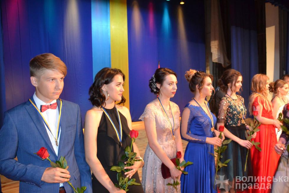 Щасливі випускники з квітами й медалями