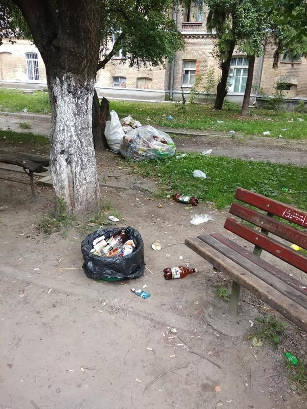 Пляшки й пакети зі сміттям валяються поруч з лавкою