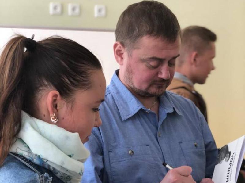 Письменник Андрій Кокотюха підписує читачці книгу