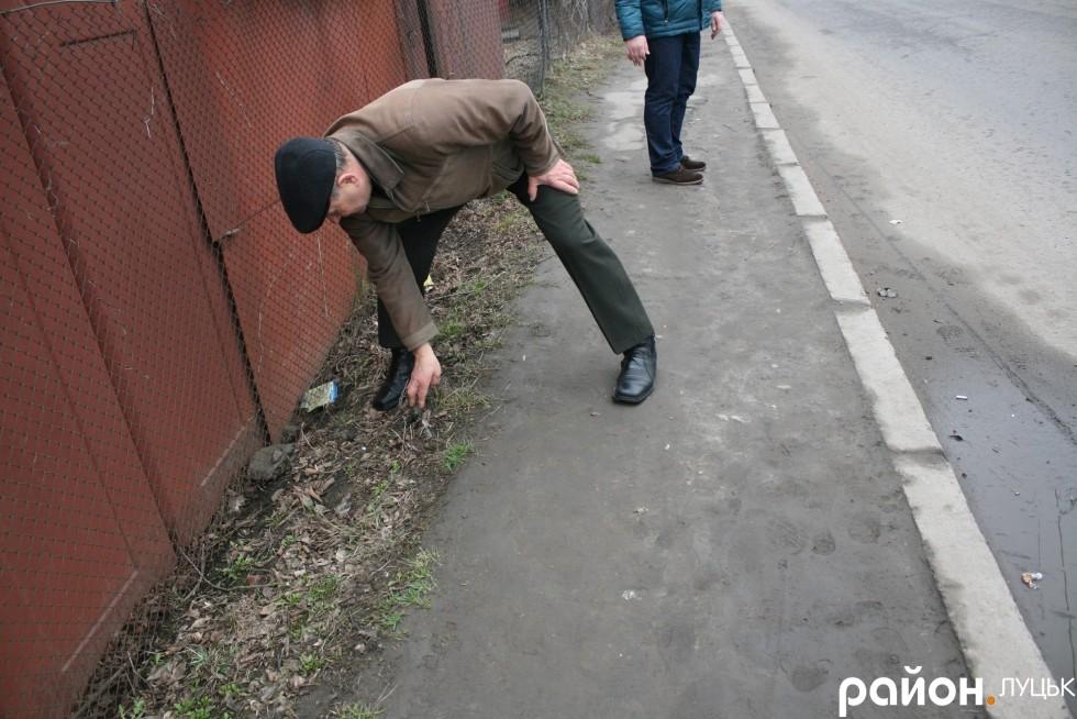 Микола Кухарчук показує частини асфальту колишнього тротуару, який знищили, щоб поставити гаражі
