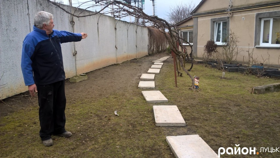 Петро Шидловський показує на паркан, який розділяє його будинок і підстанцію