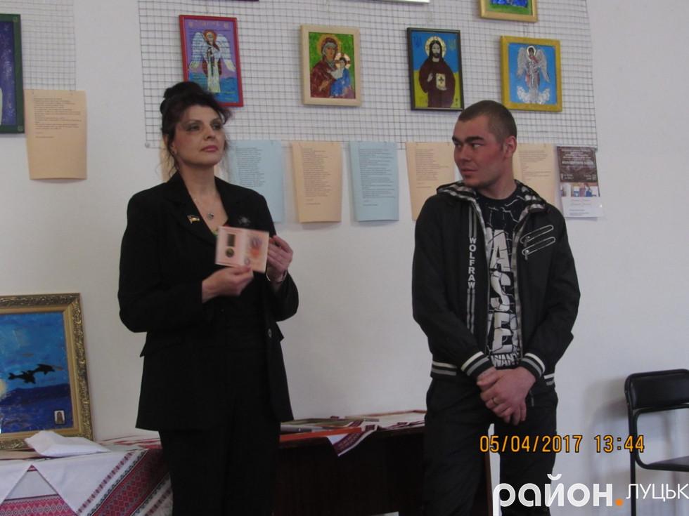 Волонтерка Iрина Захарченко нагороджує бiйця народною медаллю