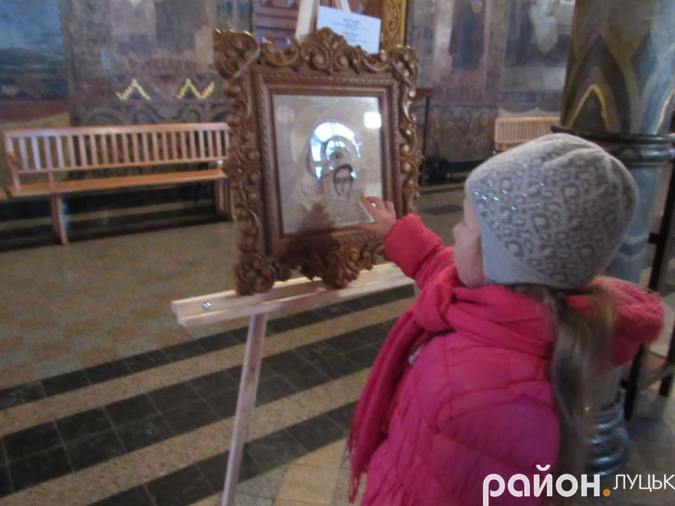 Маленька дівчинка торкається ікони