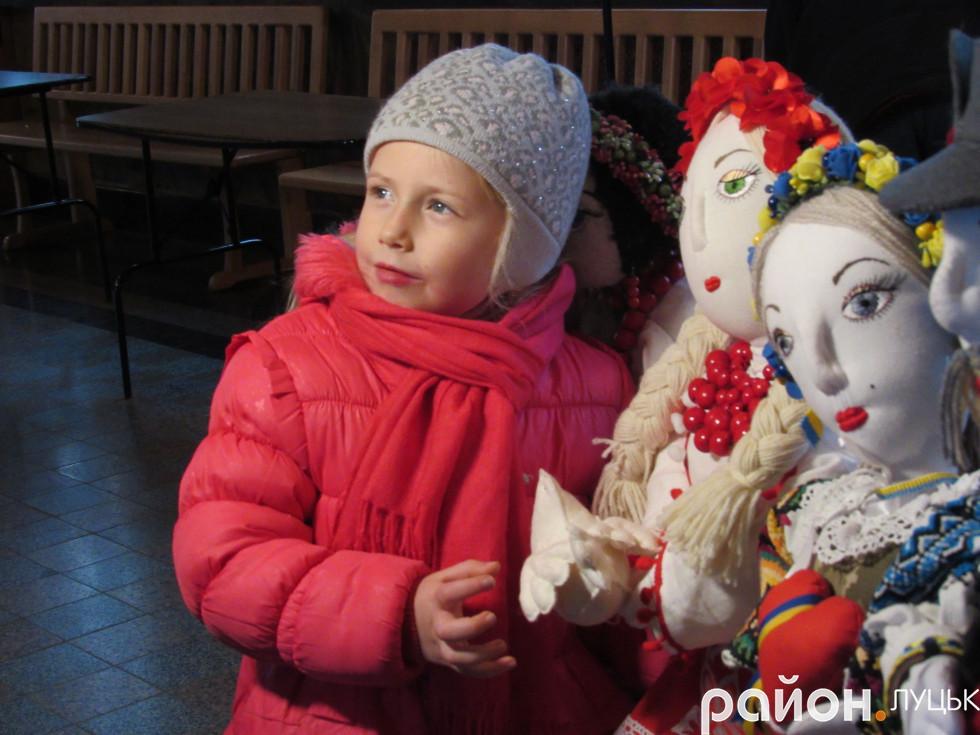 Дівчинка захоплюється ляльками майстрині