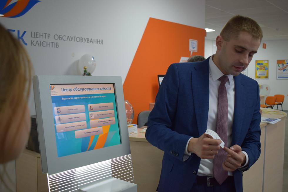 Юрій Петрук демонструє дітям, як користуватися електронною чергою