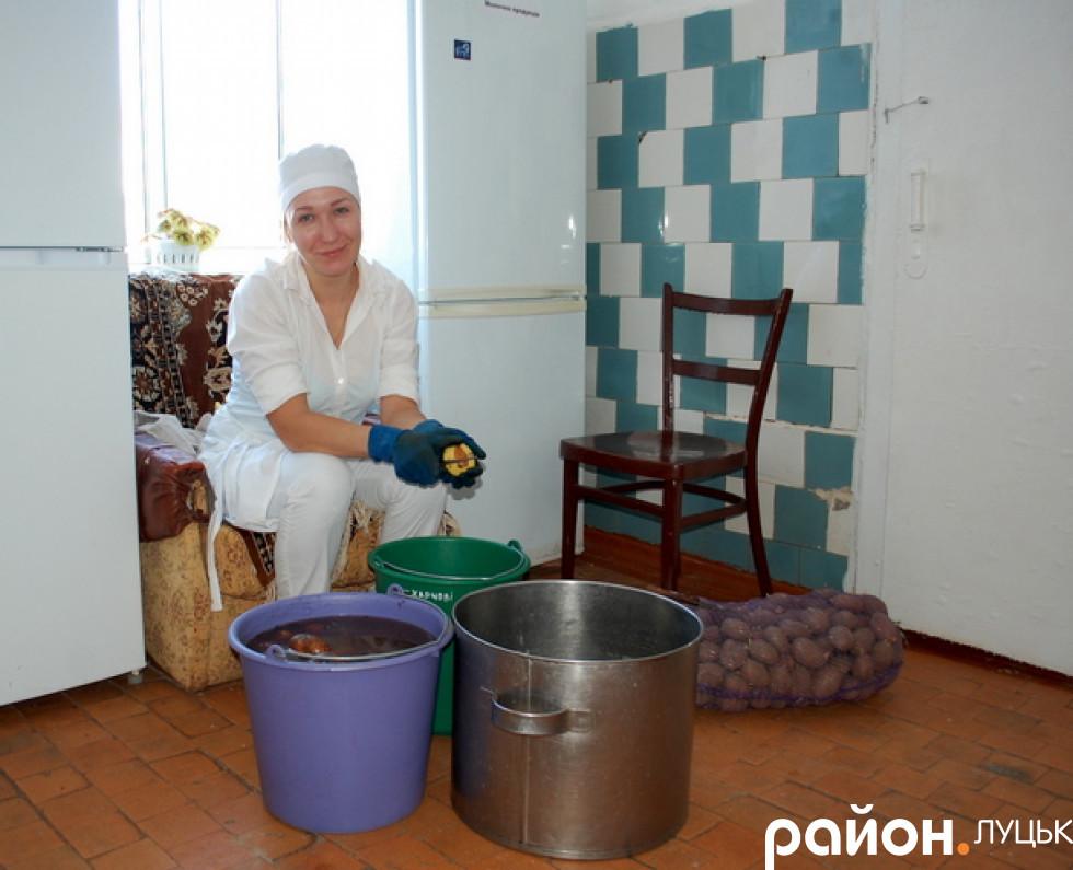 Працівники вбирають картоплю для учнів школи