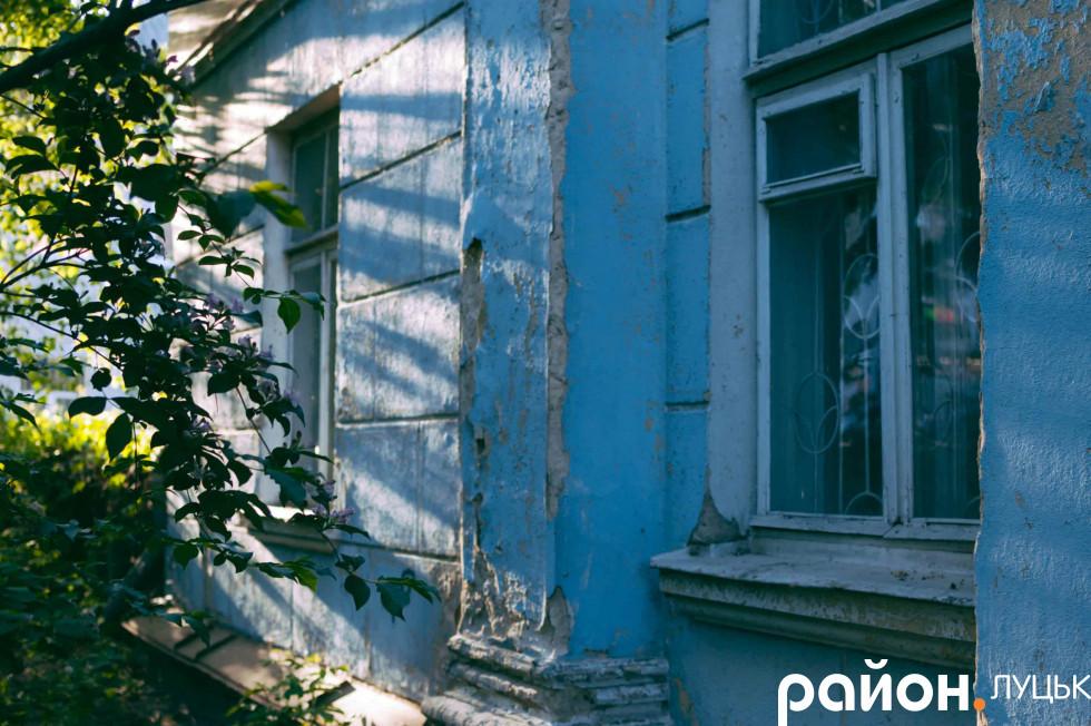 Вечірнє сонце пробивається крізь листя на стіни будинку